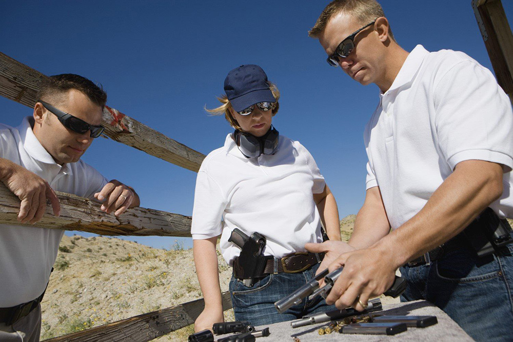 Gun trainer checking firearm prior to class with woman and man looking on
